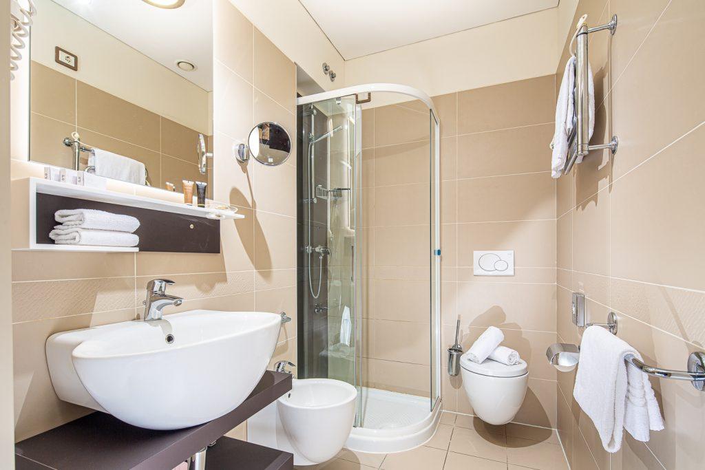 Servizio fotografico di interni in hotel con toilette, prodotti di cortesia per hotel e asciugamani piegati con cura